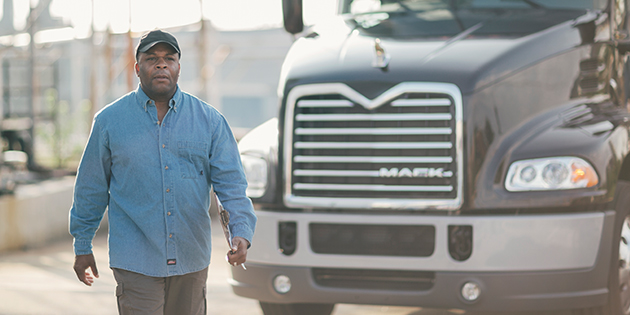 a man standing in front of a Mack truck