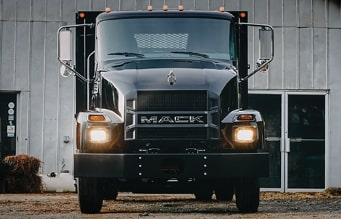 Front view of a black Mack MD Series truck parked in front of a business.