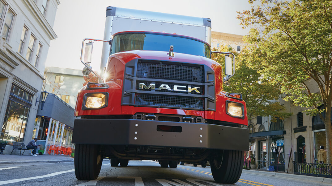 Front view of a red Mack MD Series driving on a city street.