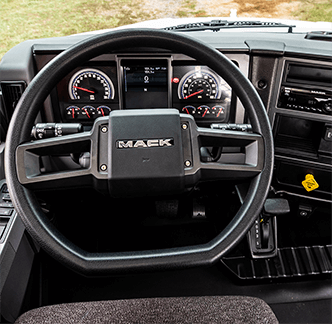 The interior of a Mack MD Series truck with a flat-bottom steering wheel.