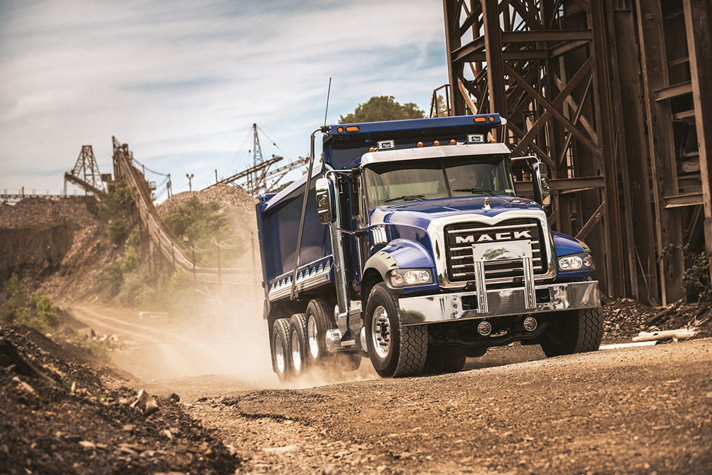 a Mack Granite dump truck on a dirt road