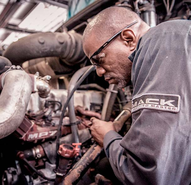 Technician working on a Mack engine