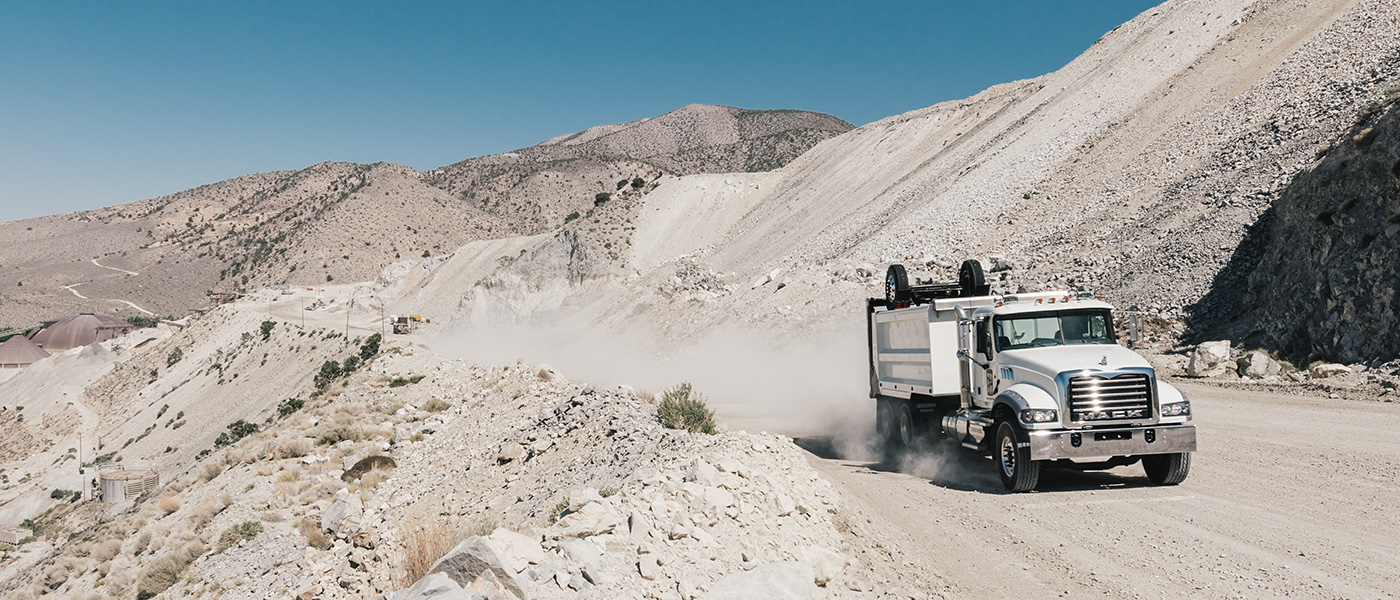 White Granite truck driving through sandy terrain